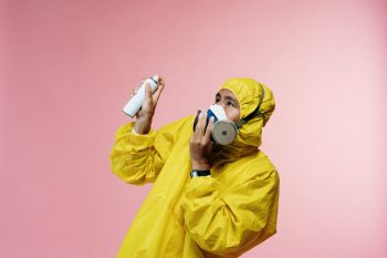 person-in-coveralls-holding-spray-bottle-3951378